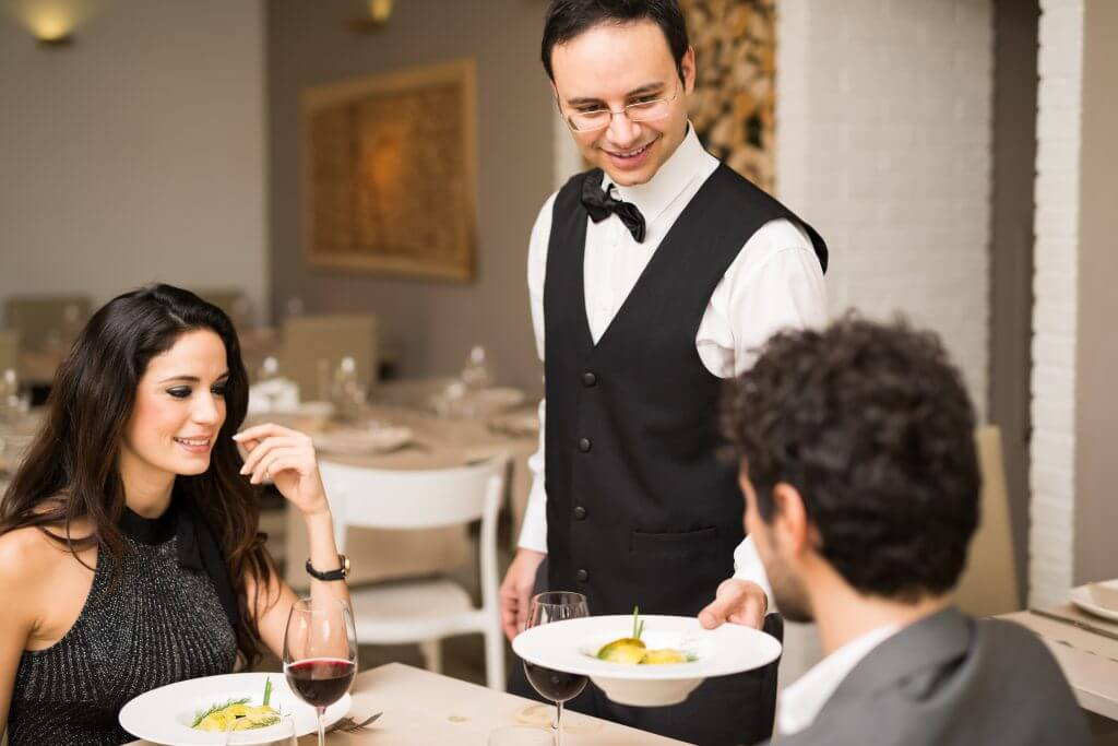 waiter serving food at a fine dining restaurant
