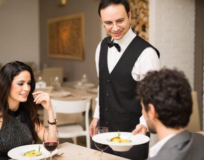 waiter serving food at a fine dining restaurant